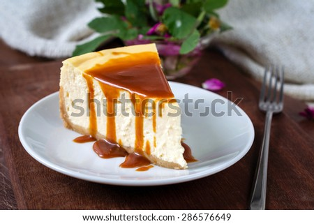 Slice of new york cheesecake with caramel sauce on wooden board with fork - stock photo