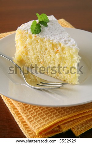 Slice of orange cake with napkin on wood table