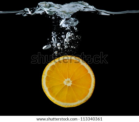 Slice of orange in the water on black background