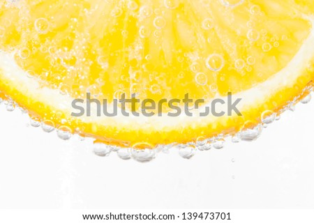 slice of orange in the water with bubbles, isolated on white - stock photo