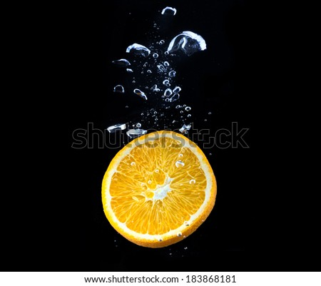 slice of orange in the water with bubbles, on black background - stock photo