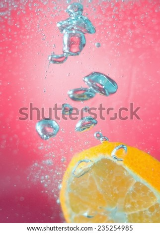 Slice of orange in the water with bubbles, on red background - stock photo
