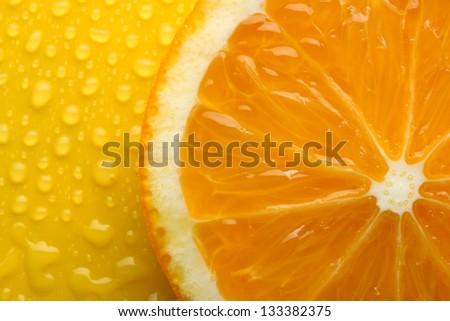 Slice of orange with drop on yellow background - stock photo
