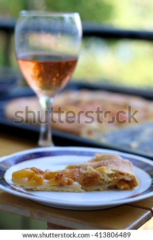 Slice of peach cake and glass of red wine outdoor. Selective focus.  - stock photo