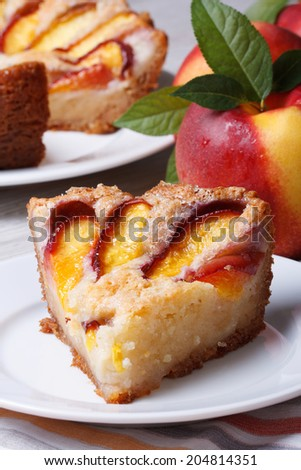 Slice of peach pie on a white plate on the table close-up. vertical   - stock photo