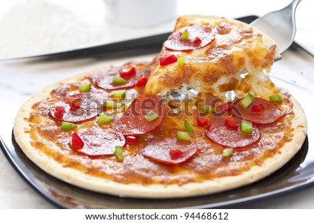 Slice of pepperoni pizza being removed Isolated over white - stock photo