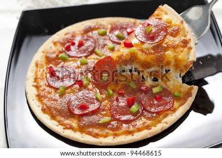 Slice of pepperoni pizza being removed Isolated over white
