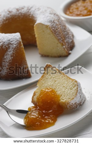 Slice of plumcake with marmelade on whithe wooden table - stock photo