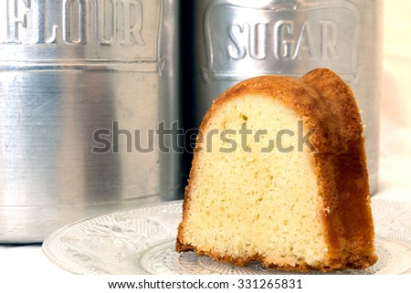 Slice of pound cake closeup with flour and sugar canisters in background. - stock photo