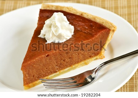 Slice of pumpkin pie with fresh whipped cream - stock photo