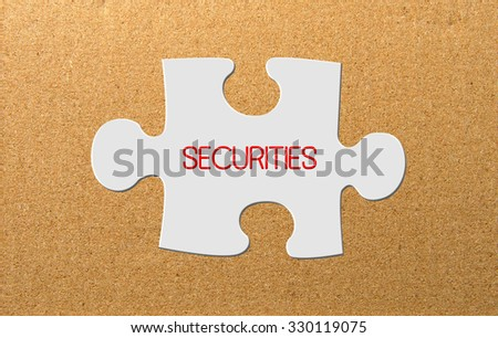 Slice of puzzle with words SECURITIES concept over cork board background. - stock photo
