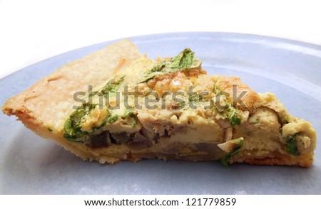 Slice of quiche with artichoke and arugula - stock photo