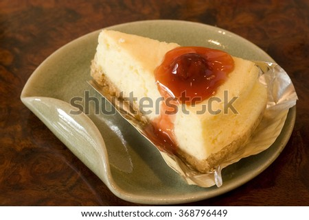 Slice of raspberry cheese cake and sauce on green dish.