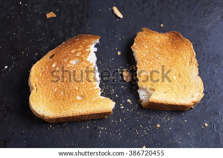 Slice of roasted white bread on black background close up. Conceptual photo - stock photo