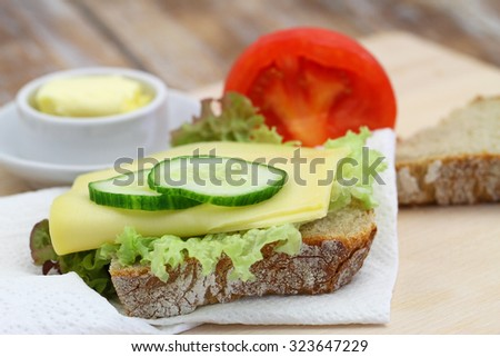 Slice of rustic rye bread with cheese lettuce and cucumber