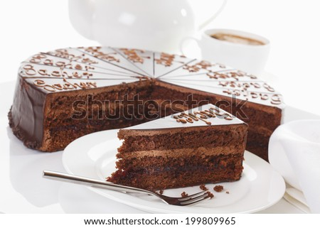 Slice of Sacher cake in plate with coffee - stock photo
