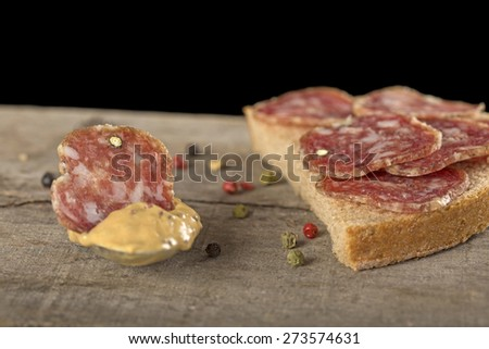 Slice of salami in mustard sauce with seeds and one salami sandwich with black background - stock photo