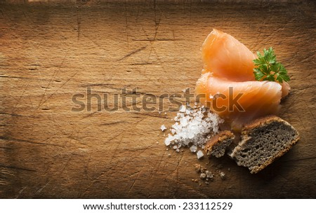 Slice of smoked salmon with sea salt and bread on wooden background - stock photo