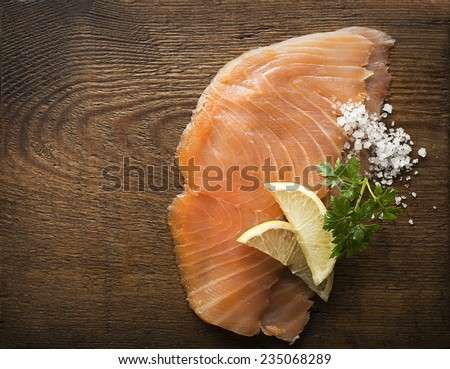 Slice of smoked salmon with sea salt and parsley - stock photo
