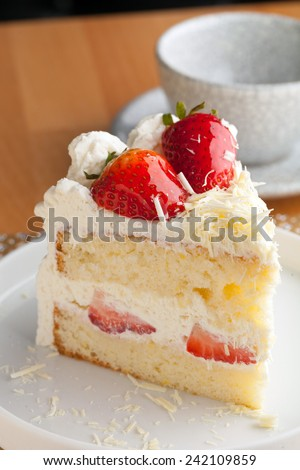 Slice of strawberry shortcake with white chocolate shavings. - stock photo