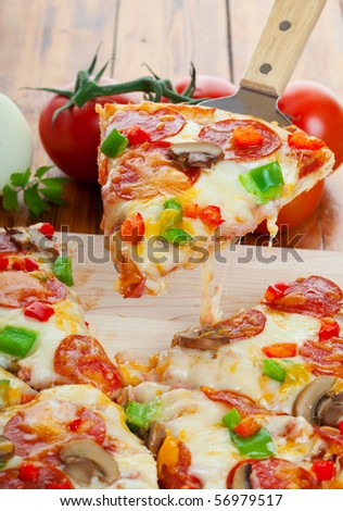 Slice of supreme pizza being lifted up - stock photo