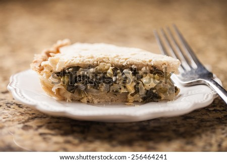 Slice of Swiss chard and onion pie fresh from the oven - stock photo