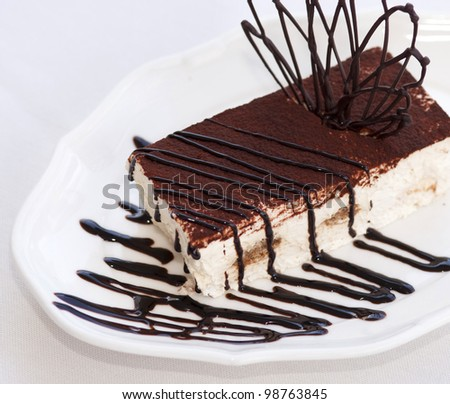 Slice of tasty chocolate tiramisu cake traditional Italian biscuit dessert on white plate on table in restaurant. Piece of unhealthy calories fat food . - stock photo