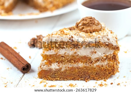 Slice of tasty gourmet vegetable carrot cake dessert food with sweet cream walnut cinnamon and raisins on white background - stock photo