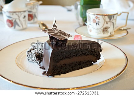 Slice of thick dark chocolate cake on gold trimmed plate with other desserts for high tea with decorative tea cups - stock photo