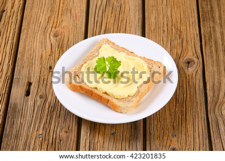 Slice of toast bread with butter on a plate - stock photo