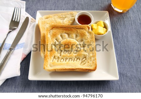 Slice of toast with Good Morning carved into it with butter and honey. - stock photo