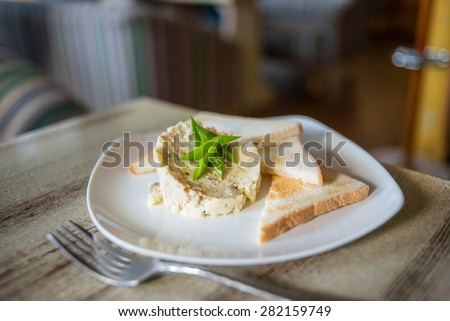Slice of toasted bread with creamy pate on wooden board - stock photo