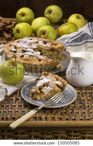 Slice of traditional american apple pie with fresh cream and green apples - stock photo