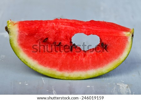 Slice of watermelon with symbol of heart cut into it - stock photo