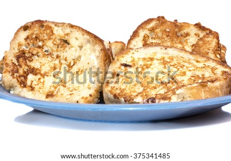 Slice of white bread toast on a white background. A butter pat in the shape of a love heart has been placed in the centre of the toast. - stock photo
