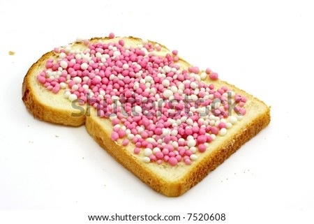 Slice of white bread with butter and little colored balls, a real dutch delicacy, isolated on white