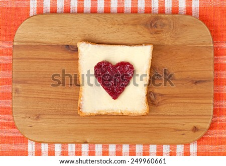 Slice of wholewheat toast with red berry jam in the shape of heart on vintage wooden background - stock photo