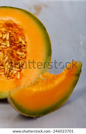 Slice of yellow melon with half melon in the backside - stock photo