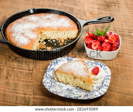 Slice of yellow skillet cake with red strawberry and cream - stock photo