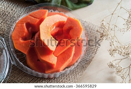 Slice papaya in plastic packaging on burlap and wooden background. - stock photo
