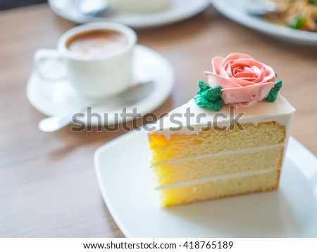 Slice Vanilla Cake With Rose Butter Cream Icing In The Plate On Wooden Table Background