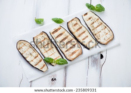 Sliced and grilled eggplant over white wooden surface, close-up - stock photo