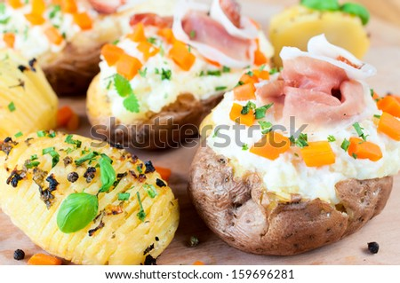 Sliced and stuffed potatoes with meat and cheese cream - stock photo