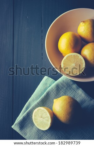 Sliced and whole lemons on wooden table - stock photo