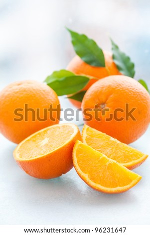 Sliced and whole orange with green leaves - stock photo