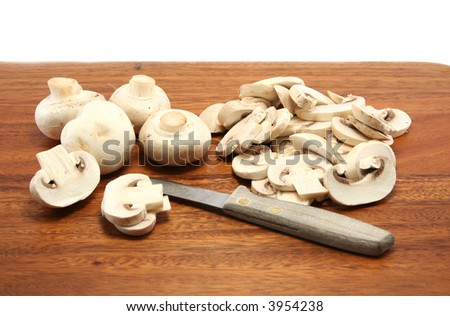 sliced and whole white button mushrooms on a wooden chopping board with a paring knife - stock photo