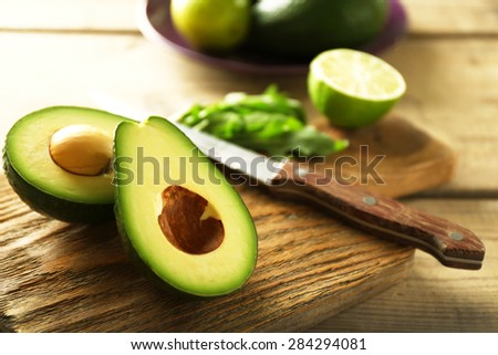 Sliced avocado and lemon lime on cutting board, on wooden background - stock photo