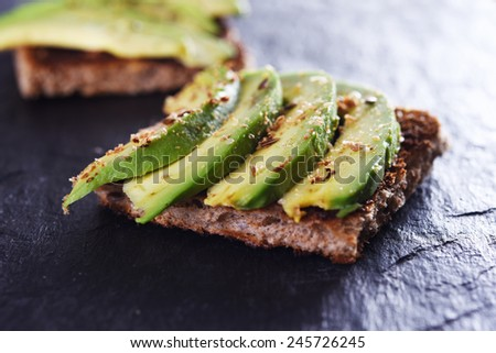 sliced avocado on toast bread with spices - stock photo