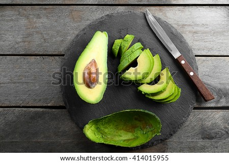 Sliced avocado with knife on slate plate - stock photo