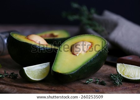 Sliced avocado with lime and herb on cutting board on black background - stock photo